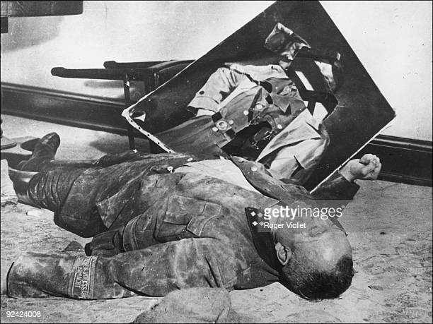 Second World War Concentration camp Liberation by the Allies Slashed portrait of Hitler German statesman near a dead guard