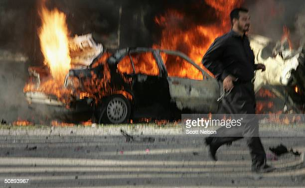 Secondary explosions rip through a vehicle as an Iraqi police officer runs past the scene of a morning car bomb attack outside the Karma hotel May 25...