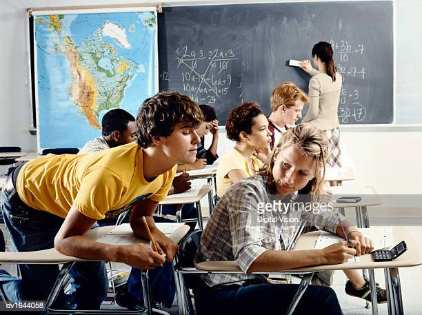 Secondary School Boy Sitting at a Classroom Desk Tries to Peek at the Test Paper of the Boy in Front of Him