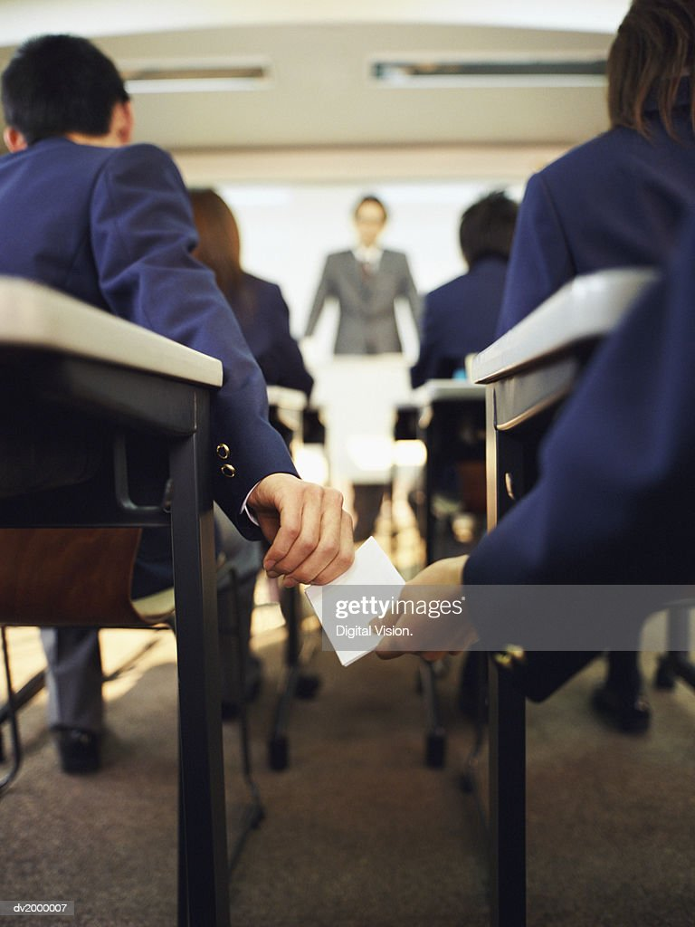 Secondary School Pupils in a Classroom Passing a Note : Stock Photo