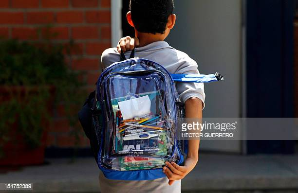 A secondary school student walks carrying a new transparent backpack in Guadalajara Mexico on October 25 2012 The transparent backpacks are part of...