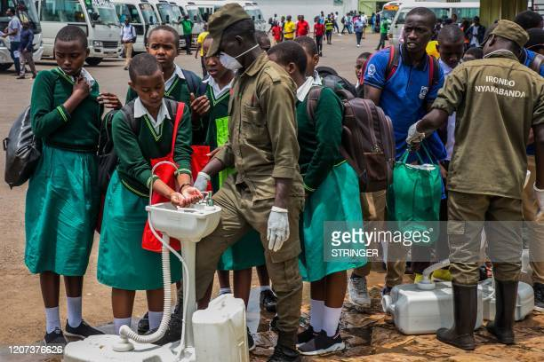 Secondary school students wash their hands at temporary hand washing point before they return home as Rwandan Government decided to send back all...