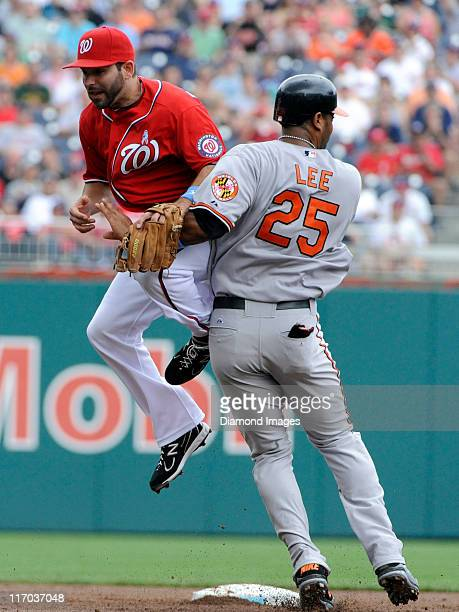 Secondbaseman Danny Espinosa of the Washington Nationals can't reach an errant throw from thirdbaseman Ryan Zimmerman and he collides with...