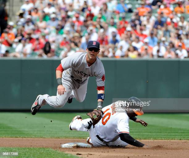 Secondbaseman Dustin Pedroia of the Boston Red Sox leaps over outfielder Adam Jones of the Baltimore Orioles after making the relay throw to...