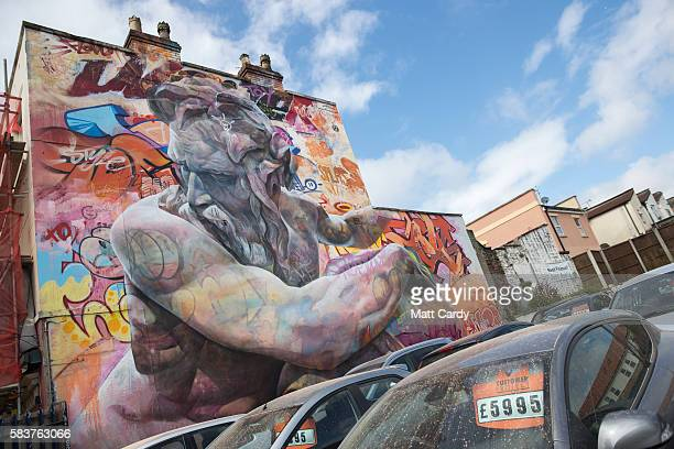 Secondhand cars are offered for sale at a car dealer below artwork by Spanish artists Pichi Avo that is part of the 2016 Upfest on July 27 2016 in...