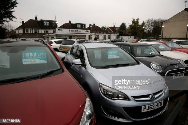 Secondhand cars sit on the forecourt of MJA Car Sales in SunburyonThames West of London on January 26 2017 / AFP PHOTO / Adrian DENNIS