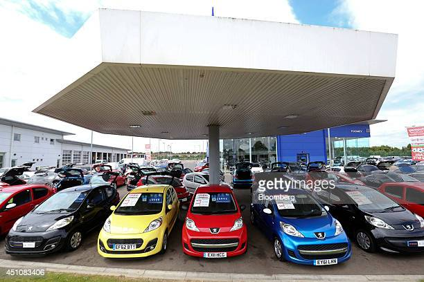 Secondhand Peugeot automobiles produced by PSA Peugeot Citroen stand parked for sale outside Toomey Motor Group's car dealership in Rochford UK on...