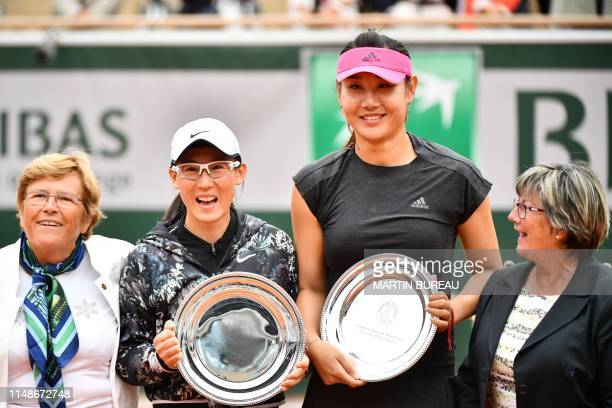 Secondplaced China's Duan YingYing and compatriot Zheng Saisai pose with their trophy after the women's doubles final match against France's Kristina...