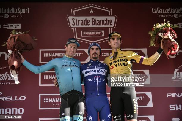 Second-placed Denmark's Jakob Fuglsang, winner Julian Alaphilippe and third-placed Belgium's Wout Van Aert celebrate on the podium after the one-day...