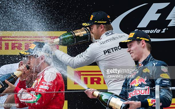 Second-placed Ferrari's German driver Sebastian Vettel , winner Mercedes AMG Petronas F1 Team's German driver Nico Rosberg and third-placed Red Bull...