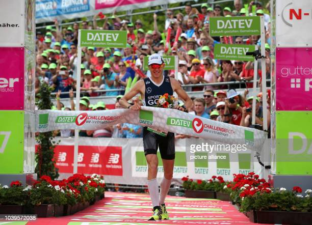 Secondplaced German triathlete Timo Bracht crosses the finish line of the Datev Challenge Roth in Roth Germany 12 July 2015 Bracht finished the 14th...