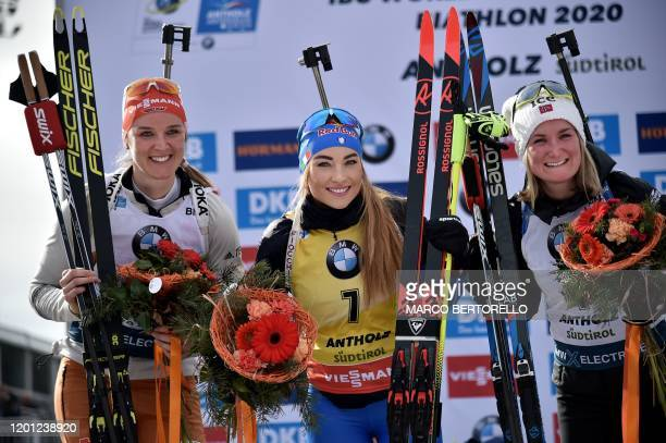 Secondplaced Germany's Denise Herrmann winner Italy's Dorothea Wierer and Norway's Marte Olsbu Roeiseland pose on the podium after the IBU Biathlon...
