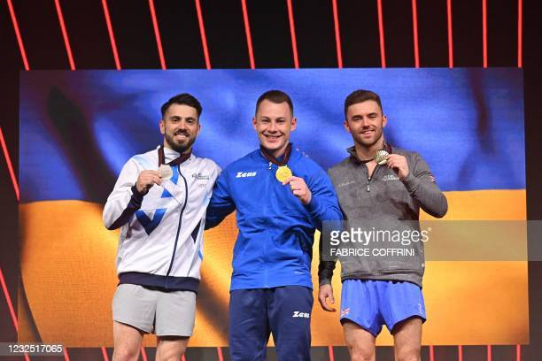 Second-placed Israel's Andrey Medvedev, first-placed Ukraine's Igor Radivilon and third-placed Britain's Giarnni Regini-Moran celebrate on the podium...
