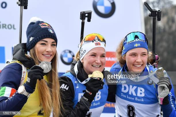 Secondplaced Italian Dorothea Wierer winner Norwegian Marte Olsbu Roiseland and thirdplaced Swedish Hanna Oberg celebrate with their medal on the...