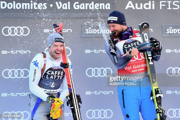 Secondplaced Italy's Christof Innerhofer winner Norway's Aksel Lund Svindal spray champagne as they celebrate on the podium after the FIS Alpine...
