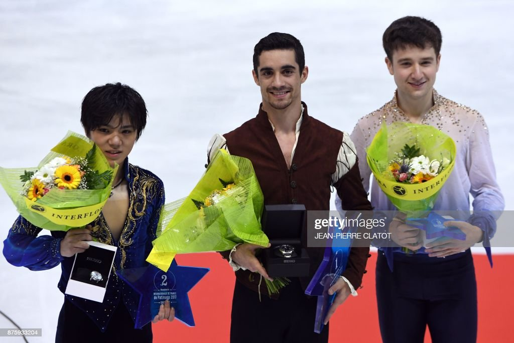 Second-placed Japan's Shoma Uno, first-placed Spain's Javier Fernandez, third-placed Uzbekistan's Misha Ge celebrate on the podium during the prize ceremony after competing in the Men Free Skating as part of the Internationaux de France ISU Grand Prix of Figure Skating in Grenoble, central-eastern France, on November 18, 2017. /