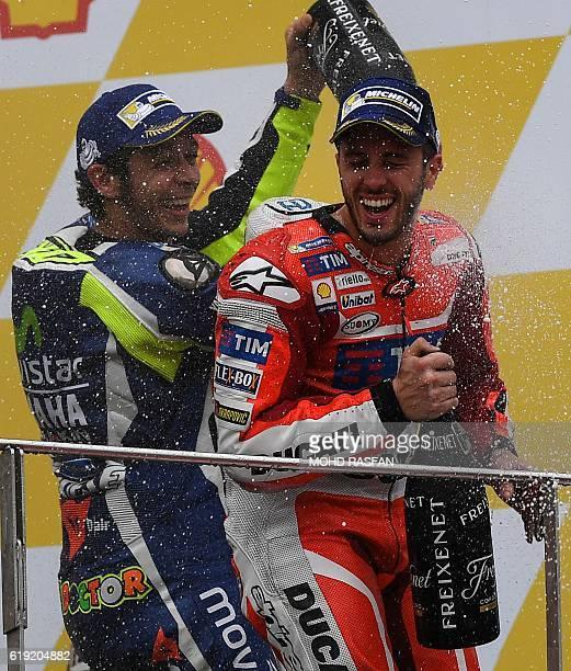 Secondplaced Movistar Yamaha MotoGP's Italian rider Valentino Rossi pours champagne on Ducati Team's Italian rider and race winner Andrea Dovizioso...
