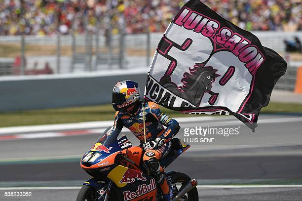 Secondplaced Red Bull KTM Ajo Moto3 South African rider Brad Binder waves a tribute flag to SAG Team Moto2 Luis Salom after the Moto3 race at the...
