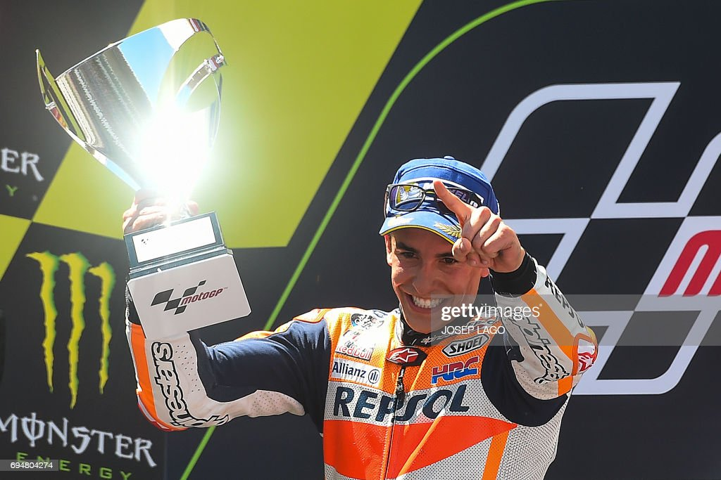 Second-placed Repsol Honda Team's Spanish rider Marc Marquez celebrates on the podium with the trophy after the Moto GP race of the Catalunya Grand Prix at the Montmelo racetrack near Barcelona on June 11, 2017. / AFP PHOTO / Josep LAGO