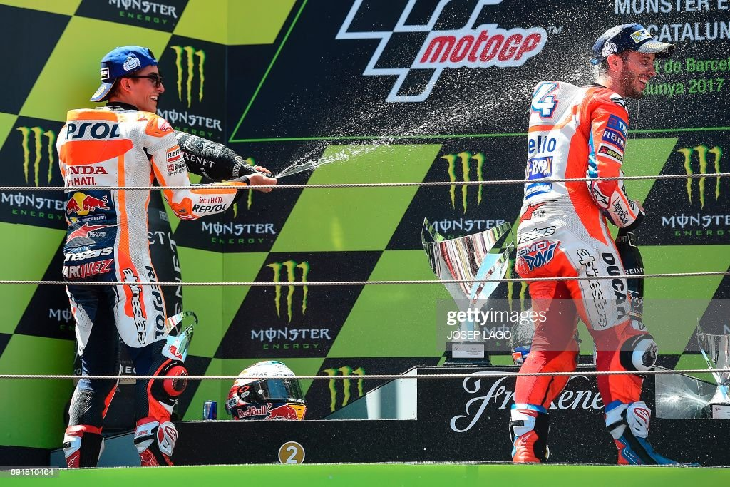 Second-placed Repsol Honda Team's Spanish rider Marc Marquez sparys cava on first-placed Ducati Team's Italian rider Andrea Dovizioso on the podium after the Moto GP race of the Catalunya Grand Prix at the Montmelo racetrack near Barcelona on June 11, 2017. / AFP PHOTO / Josep LAGO