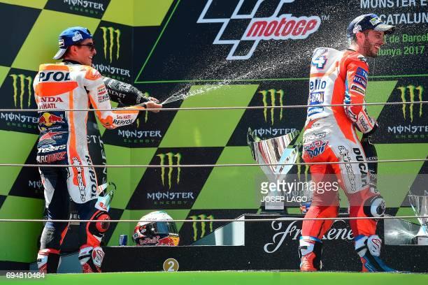 Secondplaced Repsol Honda Team's Spanish rider Marc Marquez sparys cava on firstplaced Ducati Team's Italian rider Andrea Dovizioso on the podium...