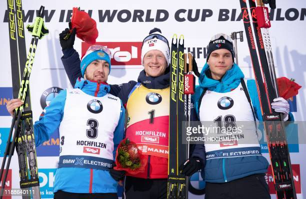 Secondplaced Russia's Alexander Loginov winner Norway's Johannes Thingnes Boe and thirdplaced French Emilien Jacquelin celebrate on the podium after...