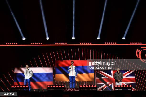 Second-placed Russia's Nikita Nagornyy, firt-placed Armenia's Artur Davtyan, and third-placed Britain's Joe Fraser celebrate on the podium during the...