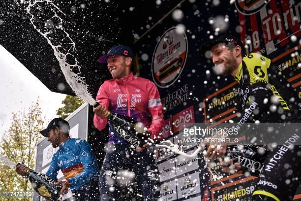 Secondplaced Spain's Alejandro Valverde race winner Canada's Michael Woods and thirdplaced Britain's Adam Yates spray champagne as they celebrate on...