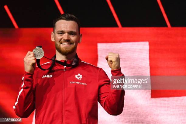 Second-placed Switzerland's Benjamin Gischard celebrates on the podium with the silver medal during the award ceremony after competing in the Men's...