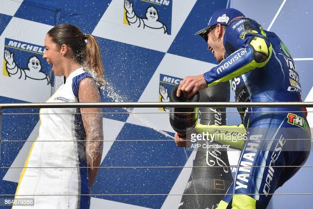 Second-placed Yamaha rider Valentino Rossi of Italy sprays a podium girl with champagne as he celebrates at the end of the Australian MotoGP Grand...