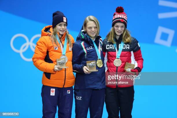 Secondplaced Yara van Kerkhoff from the Netherlands firstplaced Arianna Fontana from Italy and thirdplaced Kim Boutin from Canada standing on the...