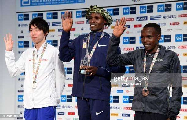 Secondplaced Yuta Shitara of Japan and thirdplaced Amos Kipruto of Kenya wave with firstplaced Dickson Chumba of Kenya as they pose for photographers...