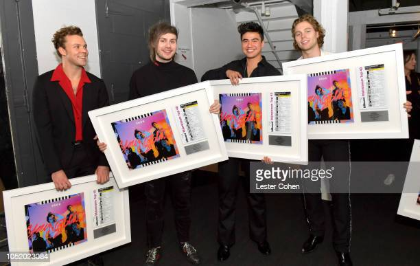 Seconds of Summer band members Luke Hemmings Calum Hood Michael Clifford and Ashton Irwin are presented with plaques to commemorate 1 million...