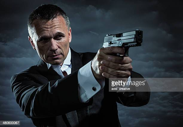 secret agent armed with handgun - dinner jacket stock pictures, royalty-free photos & images