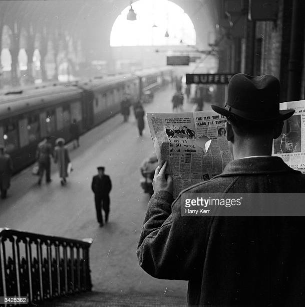 A secret service agent on duty at a railway station looking through a spy hole in his newspaper
