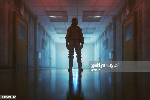 secret government underground facility with standing man in hazmat suit - conspiracy stock pictures, royalty-free photos & images