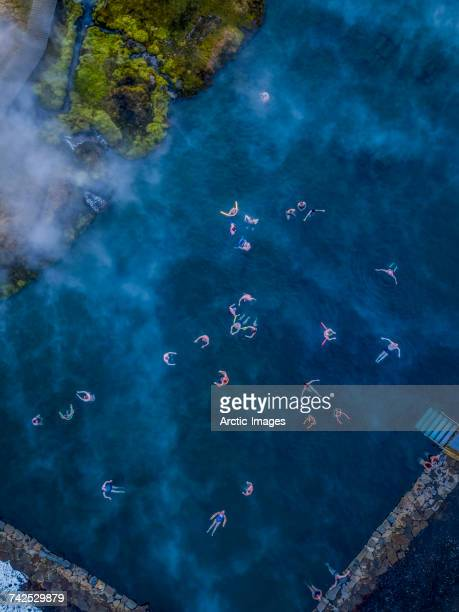 Secret Lagoon- Natural Hot Springs, Fludir, Iceland.  Aerial view of people swimming in a natural hot spring known as The Secret Lagoon, located near the small village of Fludir, a short drive from Reykjavik, Iceland. This image is shot using a drone.