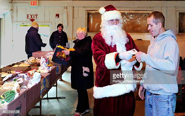 Secret Santa gives hundred dollar bills to people at Food Pantry in Alfred Here volunteer Anthony Cole of Kennebunk right gets his from the Secret...