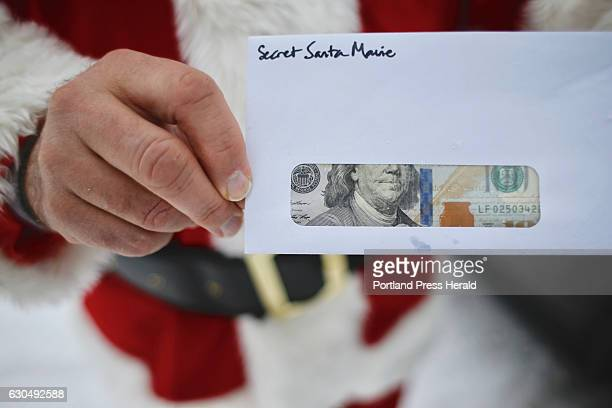 Secret Santa of Maine holds an envelope containing a $100 bill Santa and his wife who wish to remain anonymous prepared 200 such envelopes to hand to...