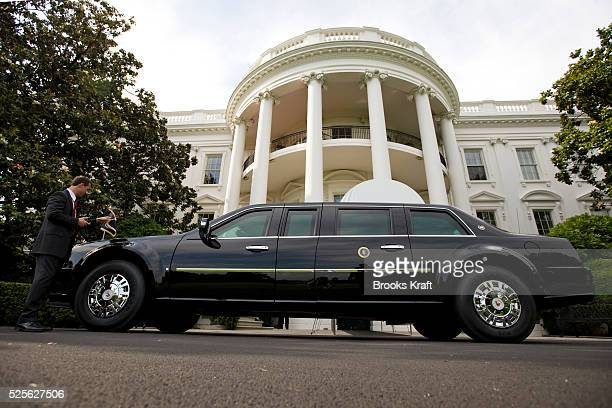 Secret Service agent adjusts a flag on the Presidential limousine in front of the White House in Washington.