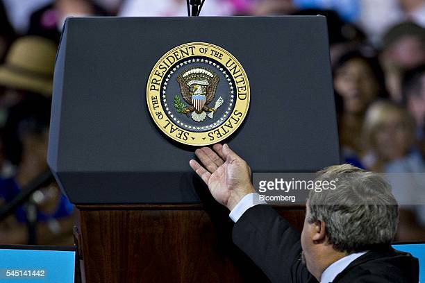 A US Secret Service agent adjusts the Presidential Seal on a podium during a campaign rally for Hillary Clinton presumptive 2016 Democratic...