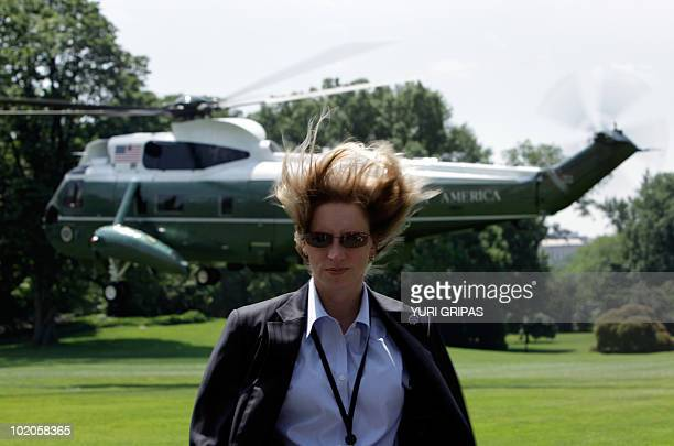 Secret Service agent fights with the wind caused by Marine One in the background with US President Barack Obama on board as it takes of on the South...