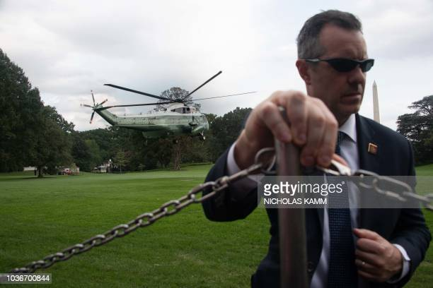 A Secret Service agent holds on as Marine One carrying US President Donald Trump takes off from the White House in Washington DC on September 20 2018