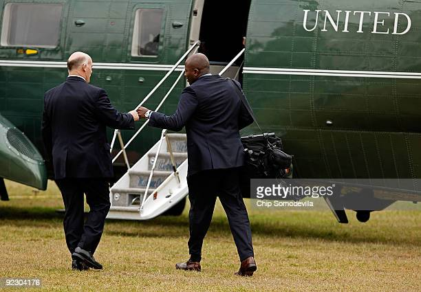 Secret Service Agent Joe Clancy greets President Barack Obama's assistant Reggie Love with a fist bump before boarding Marine One on the South Lawn...