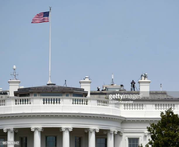 S Secret Service agent on the White House roof keeps watch on the crowd in front of the Executive Mansion in Washington DC using highpowered...