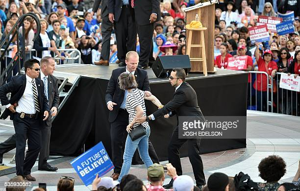 A Secret Service agent reaches for his gun as a girl who jumped a barricade is arrested during Democratic presidential candidate Bernie Sanders'...