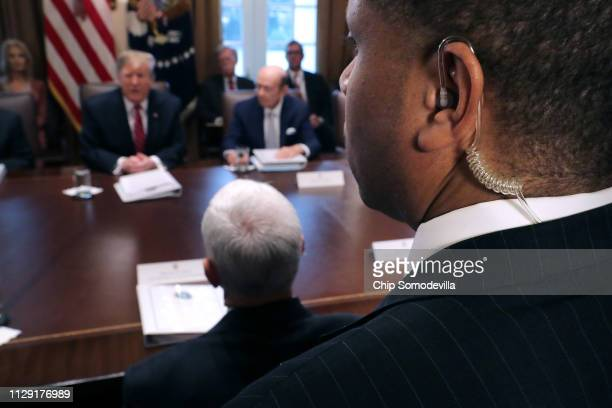 S Secret Service agent stands among journalists as President Donald Trump talks to reporters during a meeting of his cabinet in the Cabinet Room at...