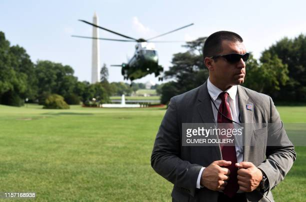 A Secret Service agent stands guard as Marine One with US President Donald Trump on board lands at the White House on July 21 in Washington DC Trump...