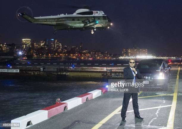 Secret Service Agent stands guard as Marine One with US President Barack Obama aboard prepares to land at the Downtown Manhattan Heliport in New York...
