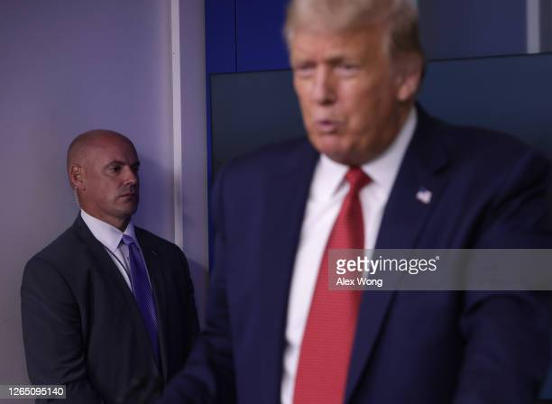 Secret Service agent stands near U.S. President Donald Trump while he speaks during a news conference at the James Brady Press Briefing Room of the...